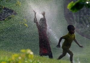 Pakistani children cool off by walking t
